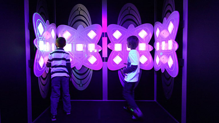 two kids playing with an interactive light game