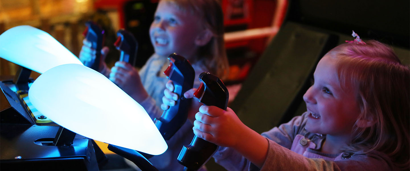 little girls playing a video game in the arcade