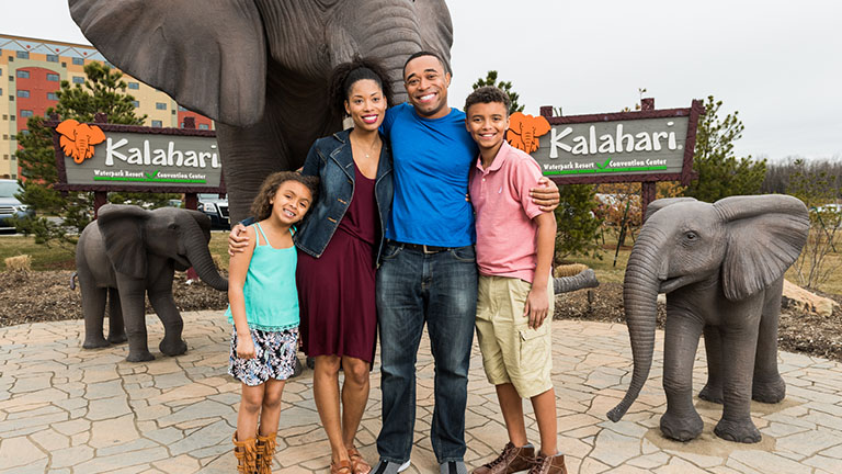 happy family taking a picture outside Kalahari in front of some elephant statues